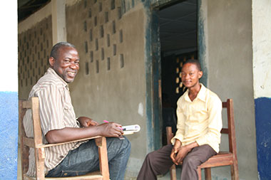 SI performance evaluation team member (L) interviews a beneficiary of a youth program (R)