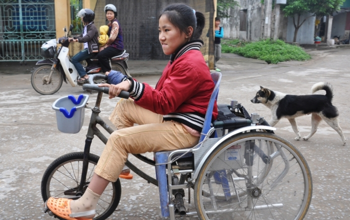 Person on a wheelchair bicycle in Vietnam.